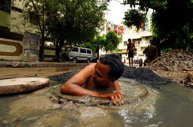 Image 2: A Conservancy worker cleaning a choked drain by manually entering a manhole in India, via The Hindu