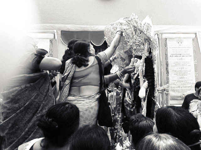 Women from the community prepare Durga for her onward journey.