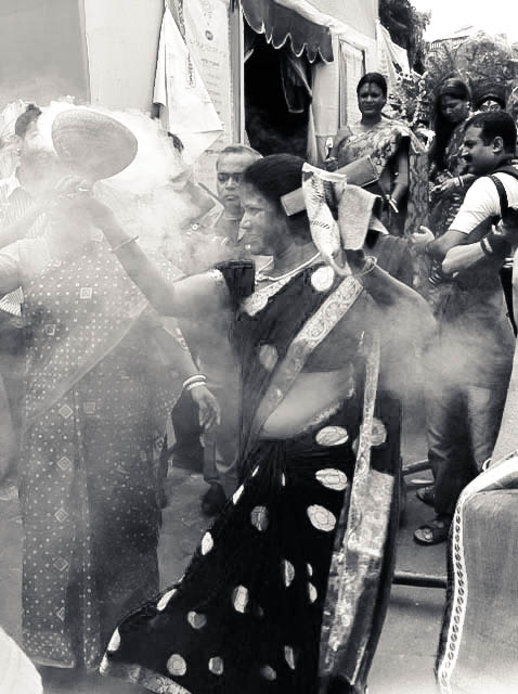 A sweet-smelling, white smoke wafts through the air as women dance. The smoke comes from earthen pots called dhunochis, which are carried by women as they dance. Burning coconut shells are placed inside the pots along with powdered incense, known as dhuno, to create the smoke.