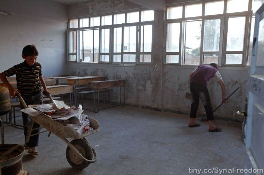 Children clean up their classrooms in a school damaged during fighting in Kansafra on October 6, 2012 (Zain Karam/Reuters).