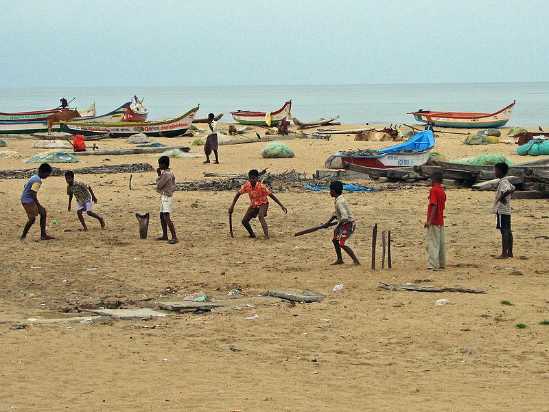 Urban poor kids playing cricket on the beach in Mahabalipuram near Chennai